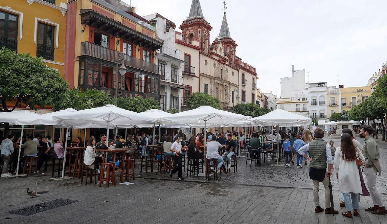 A pesar de la lluvia de las últimas horas, los sevillanos y visitantes llenan los bares del centro de la ciudad el primer dia después del fin del estado de alarma.