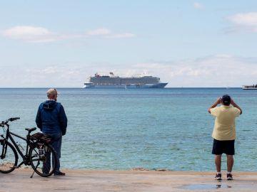 """Unos hombres observan el crucero turístico """"Odissey of the Seas"""" fondeando este lunes en la bahía de Palma de Mallorca"""