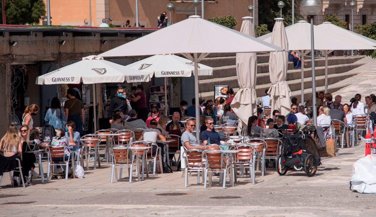 Turistas y visitantes disfrutan del sol por el centro de Palma