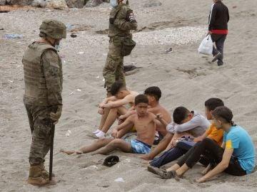 Miembros del Ejército de Tierra vigilan a un grupo de inmigrantes menores tras su entrada en Ceuta
