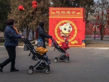 China permitirá tener 3 hijos por familia// Dos mujeres pasean con sus hijos por un parque de Pekín.