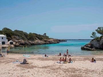 Turistas toman el sol en la playa de Binisafúller, en Menorca