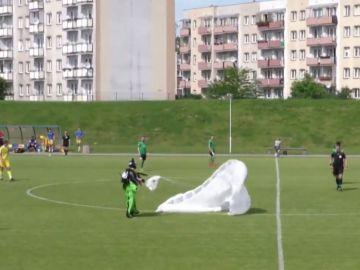 Un paracaídista aterriza en un campo de fútbol y el árbitro le saca una tarjeta amarilla