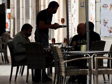 Un camarero atiende una mesa en una terraza del centro de Valencia