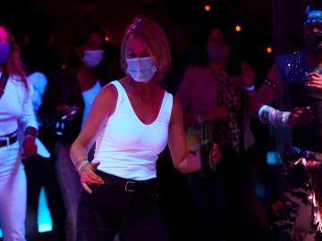 Varias personas bailan en una discoteca