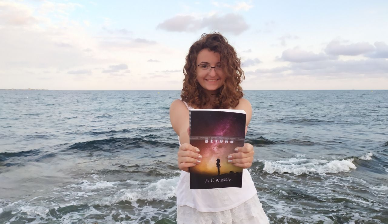 María Cuadrado sostiene su primer libro, 'Beyond', en la playa