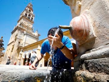 Joven se refresca en una fuente de Córdoba
