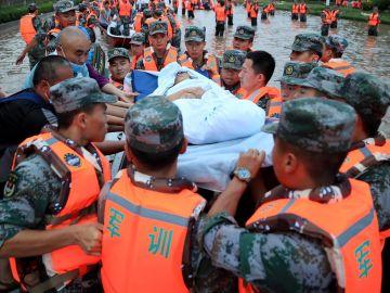 Miembros de los servicios de emergencia evacuan a los residentes de Zhengzhou (China), este jueves.
