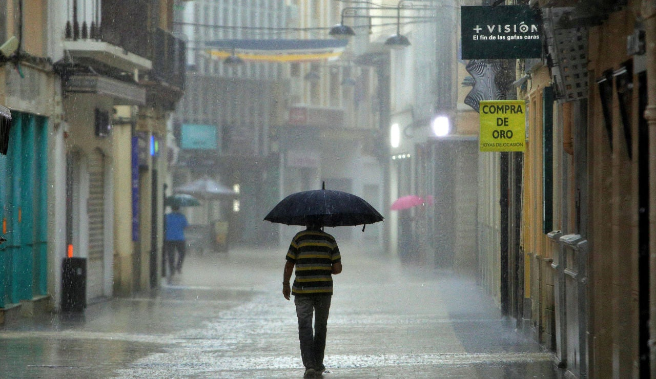 Un hombre camina, este lunes, bajo una intensa lluvia por el centro de la ciudad de Gandía.