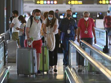 Varios turistas caminan por la terminal 4 del aeropuerto Adolfo Suárez Madrid Barajas.