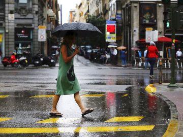 Una mujer se protege de la lluvia en el centro de Madrid.