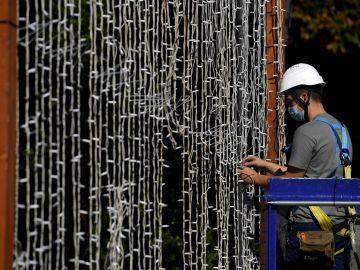 Un operario coloca una cortina de luces led en el Parque de San Francisco en Oviedo, para las próximas fiestas de la ciudad