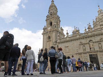 Turistas y peregrinos hacen cola para entrar a la catedral de Santiago de Compostela por la Puerta Santa