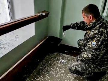 Un policía ruso recoge casquillos de bala en la universidad de Perm
