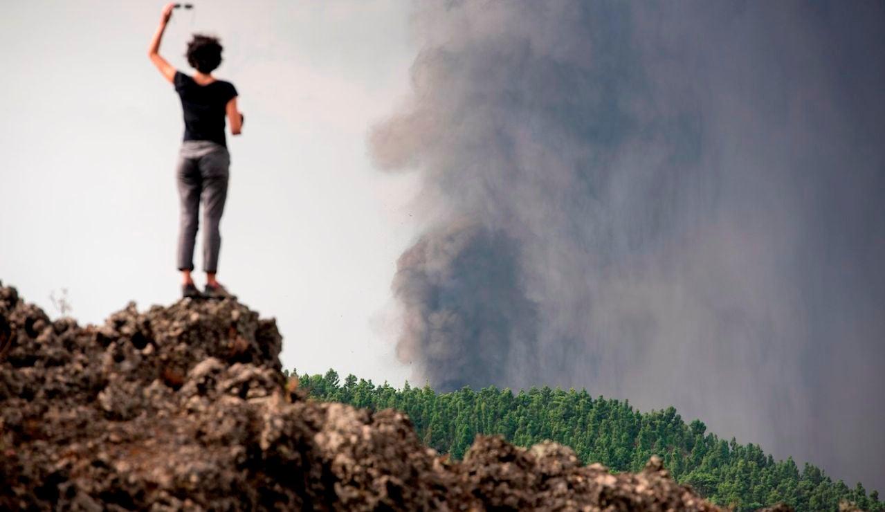 Una mujer observa la erupción de La Palma subida a una antigua colada volcánica en el municipio de El Paso.