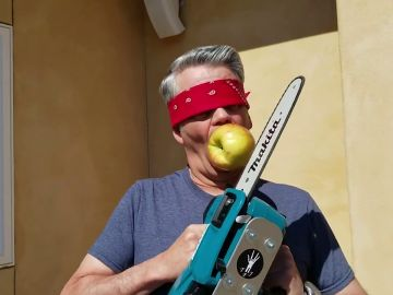 Corta una manzana con una motosierra mientras la sujeta con su boca