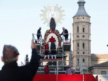 Operarios municipales colocan la Cruz de Lorena en el manto de la Virgen del Pilar de Zaragoza