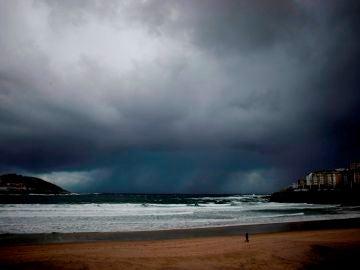Un hombre pasea a su perro por la playa del Orzán en A Coruña, en una imagen de archivo